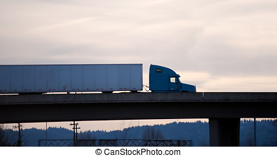 Modern semi truck trailer on overpass bridge evening silhouette