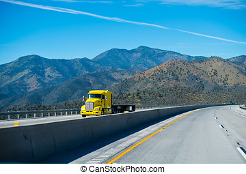Modern yellow semi truck with flat bed trailer on scenic highway mountains