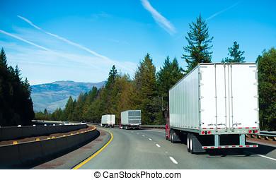 Convoy Semi trucks dry van trailers on winding highway...