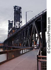 Truss lift transportation bridge with towers and walkway through evening river in heart of Portland