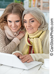 mother and daughter spending time together, using laptop