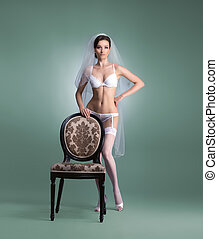 Young sexy bride in erotic lingerie over green background.
