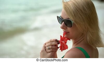 Woman staying on a beach with red flower at the evening