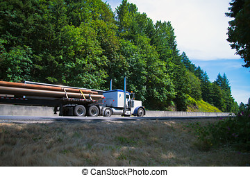 Big Rig semi truck driving highway carry long pipes on flat...