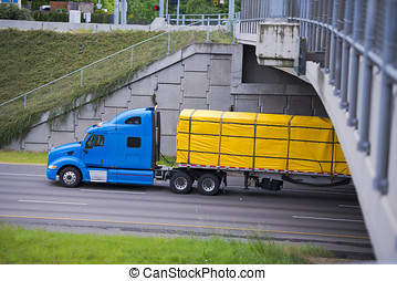 Modern blue semi truck with yellow cover cargo on trailer...