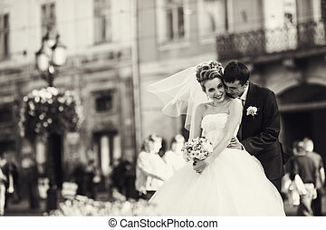 Bride looks very happy being hugged by a groom
