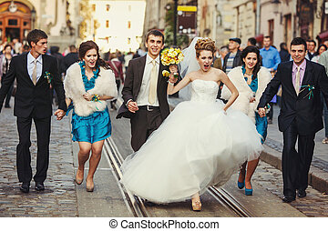 Bride with warlike spirit walks along the tramways with...