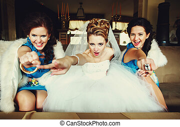 Bride and girls reach their hands out sitting on the couch