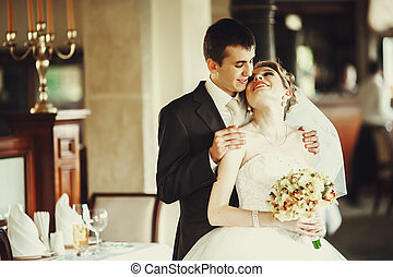 Laughing bride leans to a groom while he holds her shoulder tender