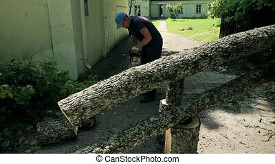 Male gardener start chainsaw and saw tree trunk fallen on house yard entrance