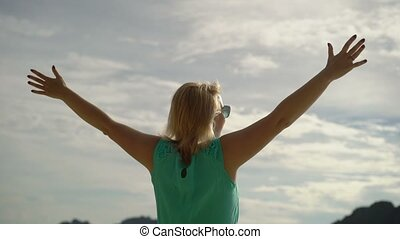 Woman walking alone on wild beach and rise hands up