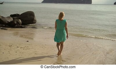 Woman walking alone on wild beach and rise hands up - Woman...