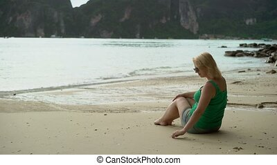 Woman sitting alone on wild beach at the evening