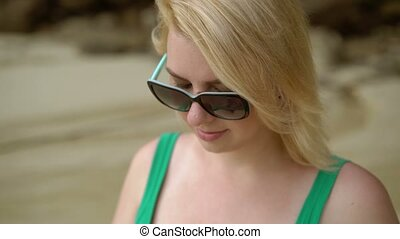 Woman staying on a beach and writing message on mobile