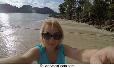 Woman staying on a beach and taking selfie - Woman staying...