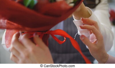 Closeup chef florists work at flowers fruit shop fixing with ribbon fruit and vegetable bouquet