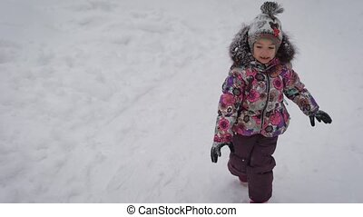 The little girl runs on a footpath of the winter forest. The...