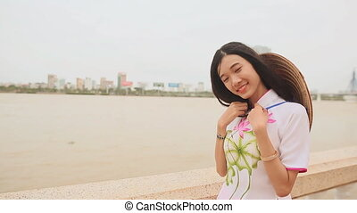 Vietnam girl in the national costume and dress Ao Dai posing on the waterfront of the city of Da Nang. On the back of the cap Non La.