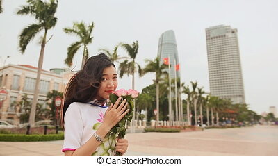 Vietnam girl in the national costume and dress Ao Dai posing against a background of skyscrapers of downtown Da Nang