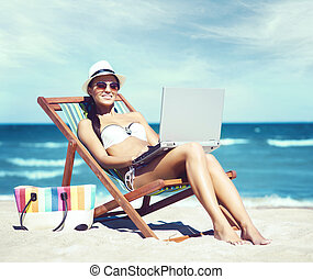 Young, beautiful, sporty and sexy woman with laptop relaxing...