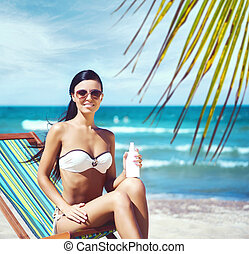 Young, beautiful, and sexy woman in white swimsuit relaxing...