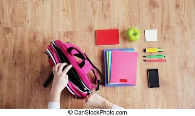 hands packing schoolbag - people, school supplies, education...