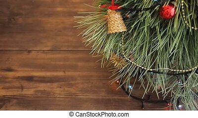 Boxes of gifts are under the tree. Gifts are Packed in colorful paper and tied with string and ribbons. Christmas garland on the fir tree branches. Tree branches close up, shift motion, panorama
