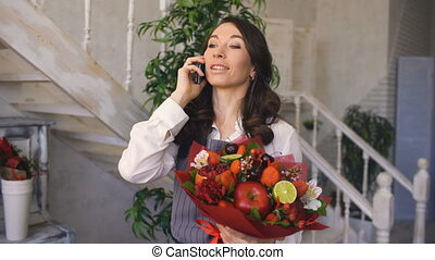 Chef woman florist call phone to her clients with floral and fruit mixed bouquet