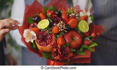 Woman rotating bouquet of fruits: lime, strawberry,...