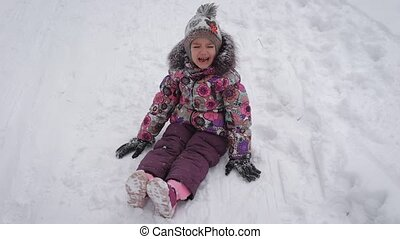 Little cute girl in warm clothes is sitting on the snow and...
