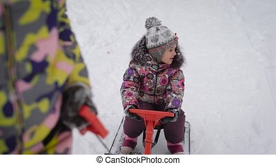 Mother ride a little girl on a sled with a steering wheel on a snow path in the park. Happy child looks around during a walk in the fresh air.
