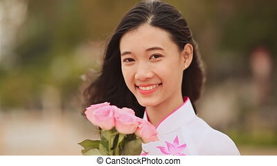 Vietnam girl in the national costume and dress Ao Dai posing and smiling for the camera. In the hands holding a pink rose.