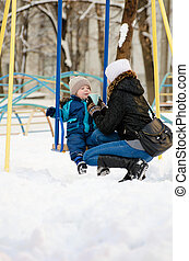 Mom gives son a cup of tea on the playground. Winter walk in...