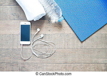 Flat lay of mobile phone with earphone and yoga mat, towel...