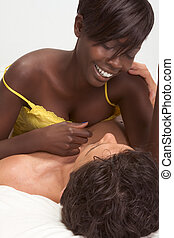Love. Sensual interracial couple in bed loving - Happy young...