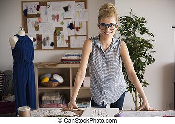 Blonde fashion designer in her workshop