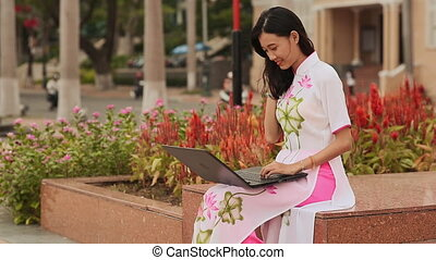 Pretty Asian girl sitting with a laptop in the street city in national dress Ao Dai
