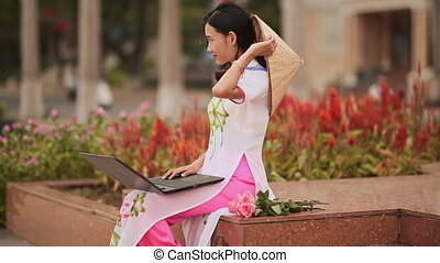 The beautiful Asian girl speaks on a laptop on the street and a beautiful national dress Ao Dai.