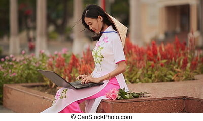 The beautiful Asian girl speaks on a laptop on the street and a beautiful national dress Ao Dai with a cap on the back of Non La