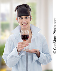 young woman drinks a glass of red wine