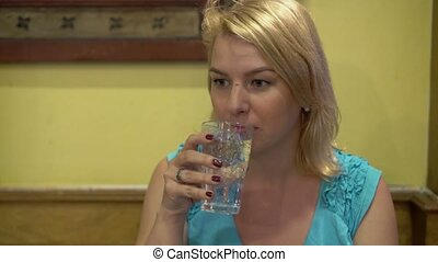 Young woman drinking water in restaurant