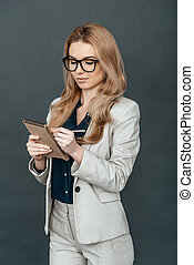 Making some notes. Attractive young woman in smart casual...
