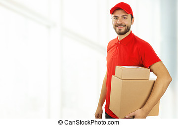 delivery man with cardboard boxes standing in office. copy...