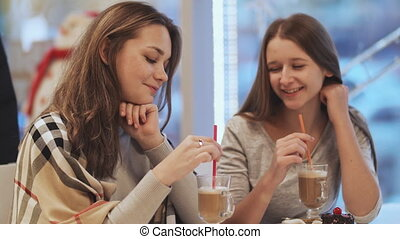 Two schoolgirls girlfriends drinking cocktails and talking in a cafe fun. Autumn, Winter.
