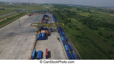 Container unloading Low-altitude airplane helicopter view of cargo train containers and rail lines in industrial areaContainer unloading