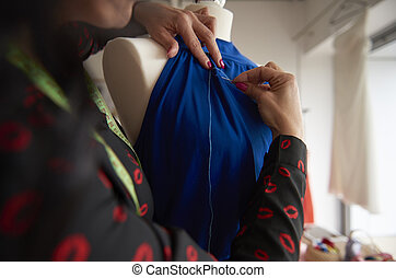 Tailor sewing a blue suit