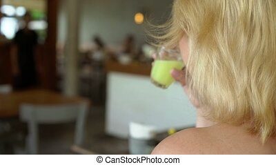 Woman drinking juice in restaurant