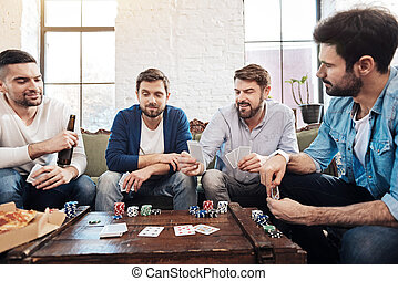 Good looking male friends playing poker - Game for true men....