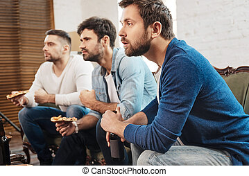 Serious concentrated men watching a football match