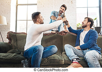 Cheerful delighted men raising bottles with beer - Time for...
